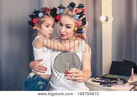 Beautiful young mother and her daughter with hair curlers are spending time together at home. Mom is showing her daughter a mirror