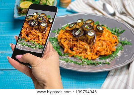 Photographing food concept - woman takes picture of pasta with eggplants, tomato, cheese, arugula and salad. The original presentation of the dish from the chef. On a blue wooden background. Photographing on a mobile phone or tablet