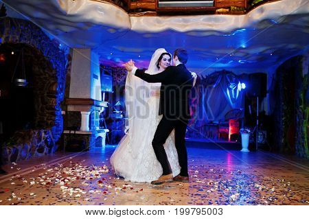 Wedding Couple Dancing Their First Dance In The Restaurant With Confetti On The Floor.