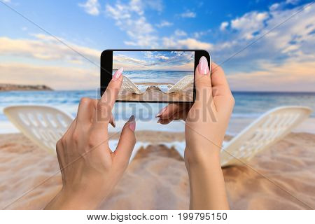 Landscape of Two Lonely beachchairs on the sand near sea in the morning at a perfect beach in Egypt. Photographing travel concept - woman takes picture of two beach chairs on the sand near sea and colorful sky
