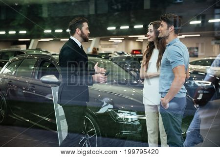 Smiling salesman showing new car to a couple in showroom salon