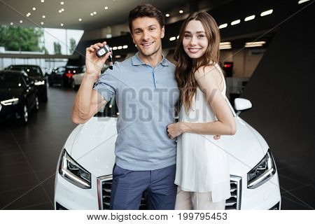 Picture of young happy woman standing near car with boyfriend in car dealership. Looking camera showing keys.