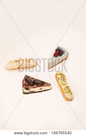 Four different delicious desserts, cakes and eclairs, isolated over white
