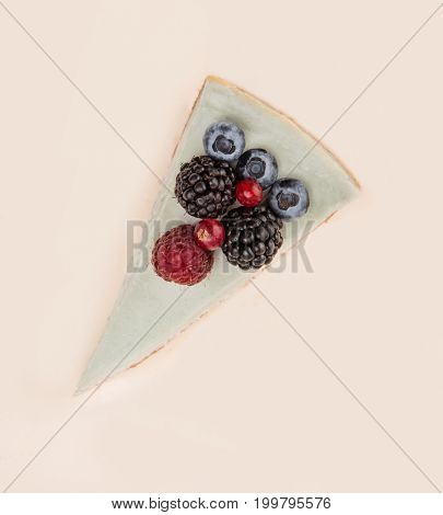 Top view of blue cheesecake with different berries on it isolated over white