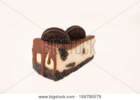 Close up of cheesecake with chocolate cream and cookie in it isolated over white