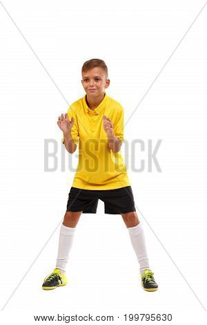 An adorable young teen in a position to catch a ball isolated over the white background. A focused sports boy in a yellow t-shirt, loose shorts and long socks. A teen playing football or soccer.