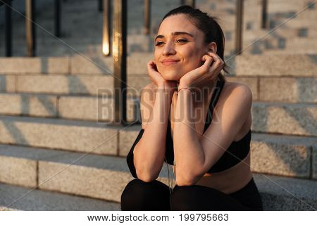 Image of smiling young sports lady sitting outdoors and looking aside.