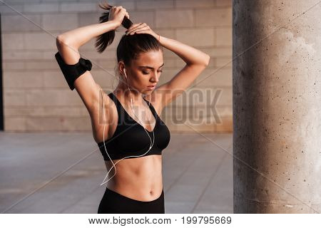 Image of concentrated young sports lady standing with earphones outdoors.