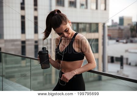 Image of pretty young sports woman standing with earphones outdoors and looking aside holding bottle of water.