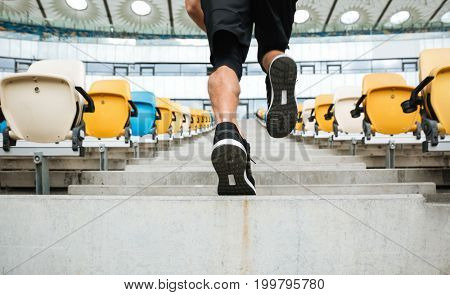 Back view close up of a male legs in sneakers running upstairs at the stadium