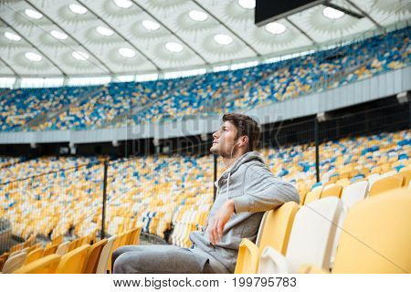 Photo of handsome young sports man at the stadium outdoors listening music and looking aside.
