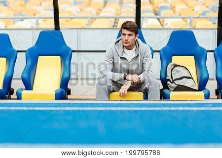 Young male athlete in sportswear sitting on a stadium seats and waiting for his coach