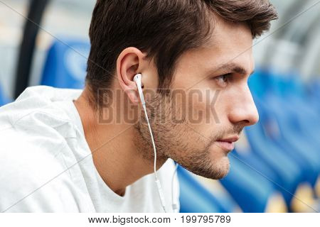 Image of serious young sports man at the stadium outdoors listening music and looking aside.