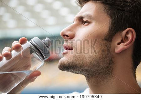 Close up profile portrait of a handsome man drinking water from a bottle at the stadium