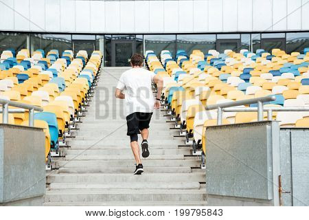 Back view of a young man running upstairs at the stadium