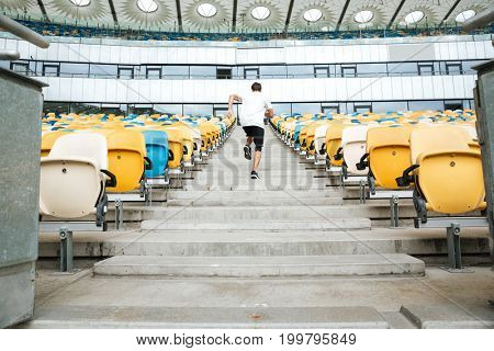 Back view of a young sportsman running upstairs at the stadium