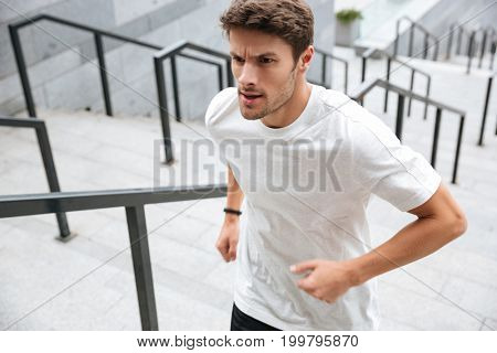 Close up of a healthy male runner in sport clothes running upstairs at the stadium