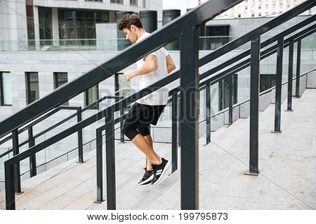 Side view of a sporty athlete man running downstairs at the stadium