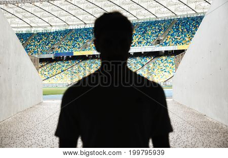 Silhouette of a man walking throught the stadium entrance