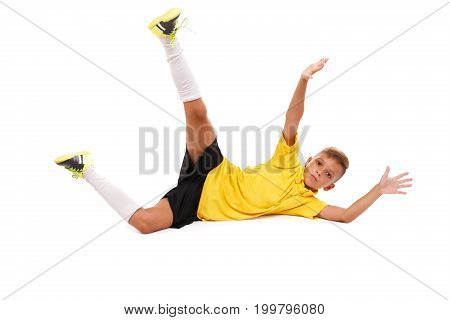 A ridiculous, funny young kid jumping to catch a ball isolated over the white background. A focused, active schoolboy playing football. Young league of professional football players.