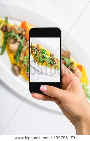 Photographing food concept - woman takes picture of baked fish King clip with vegetables and sauce, decorated of a greens salad in white plate. Close-up