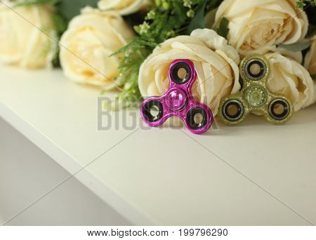 Two Fidget Spinners Pink And Green Stress Relieving Toy On White Shelf With Flowers On Background Cl