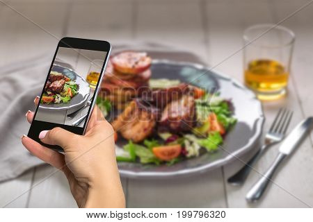 Photographing food concept - woman takes picture of hot meat dishes. Pork ribs grilled with salad and apples on a plate. Wooden background.