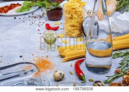 Closeup of pasta, red hot chili peppers, little quail eggs, walnuts, a glass bottle, fusilli and different seasonings on a light gray background.