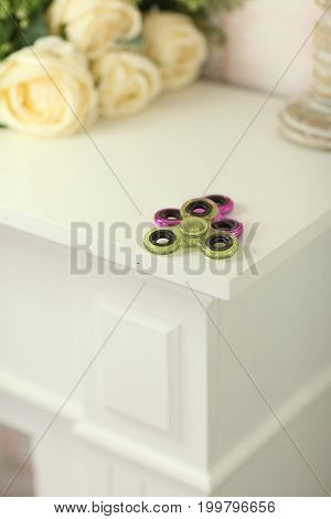 Two Fidget Spinners Pink And Green Stress Relieving Toy On White Shelf With Flowers On Background