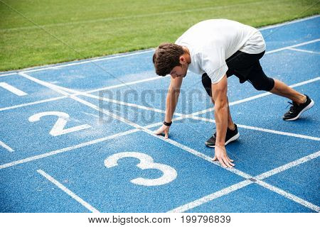 Young man standing in starting position for running on sports track at the stadium