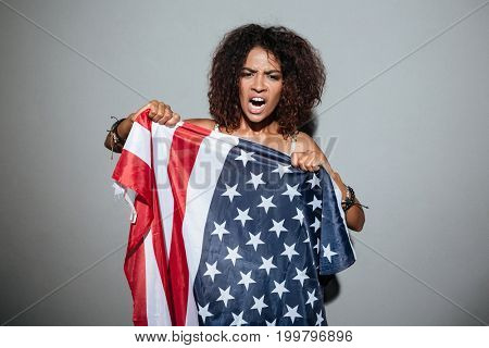 Young african woman screaming and trying to tear apart USA flag and looking at camera isolated over gray background