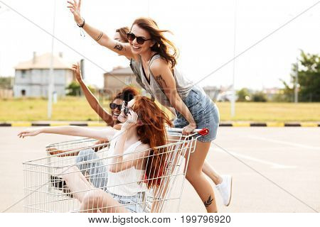 Four happy smiling girls in sunglasses having fun shopping trolley race outdoors