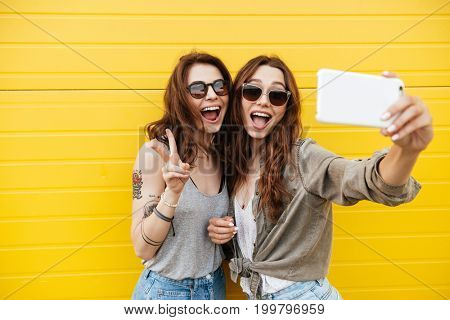 Image of two young happy women friends standing over yellow wall. Looking aside make selfie by phone.