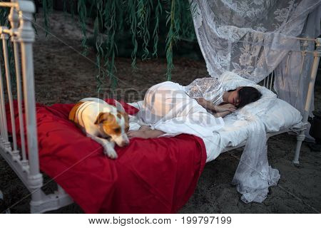 Young woman in lacy peignoir lies with dog on bed with bedding and baldachin near tree and sleeps. Concept of rest relaxation and serenity.