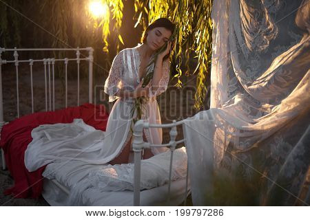 Young sexy woman in lacy peignoir kneels on bed with bedding and baldachin near tree on sunset. Concept of rest relaxation and serenity.