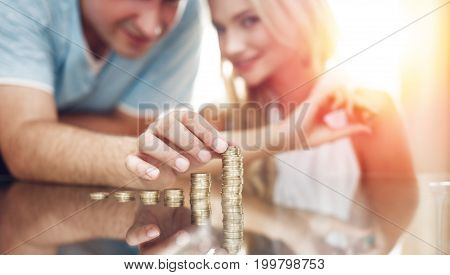 Young couple building money column on glass desk in sunset