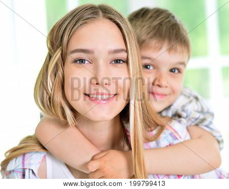 Close up portrait of little brother hugging his sister