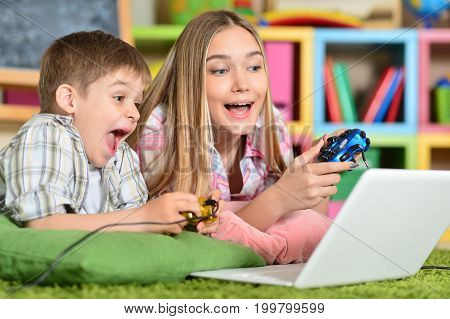brother and sister  playing computer game on laptop