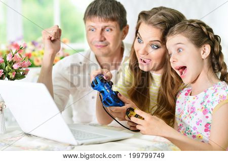 Happy family playing computer game on laptop