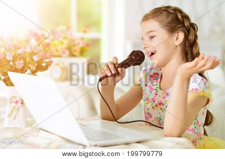 Adorable little girl using modern laptop and singing karaoke