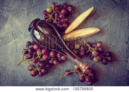Grapes with buttle of wine on wintage background