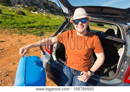 Looking at camera, a cheerful man going away for the weekend by the car with luggage.