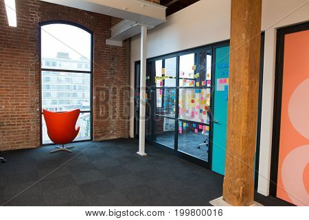View of a trendy modern open concept loft office space with big windows, natural light and a layout to encourage collaboration, creativity and innovation