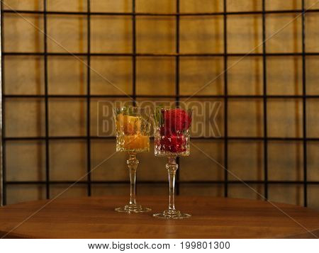Close-up picture of two portions of bright berry ice cream in crystal glasses. Refreshing sorbet scoops on a light lattice background. Summer desserts with decorative mint leaves. Copy space.