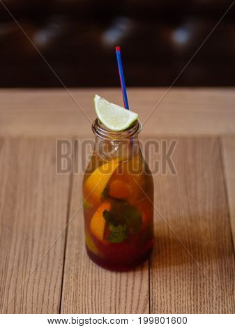 A wooden table with a fresh cocktail, cool juice, slices of oranges and green sappy leaves of mint on a blurred dark wooden background. Cold alcohol drinks.
