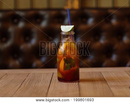 A moist glass bottle of a cool cocktail, green slices of lime, yellow fragrant lemon, verdant leaves of mint on a wooden table on a blurred brown background. Summer beverages.