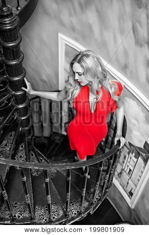 Black white and red portrait. Beautiful blond woman wearing fashion red dress staying on the spiral staircase