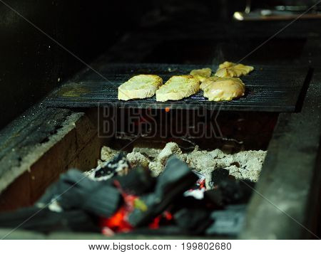 Close-up of tasty juicy pieces of grilled chicken. Fried meat on a blurred  B-B-Q background. Tender smoky fillet with firewood. Outdoors, nature, cooking concept. Copy space.