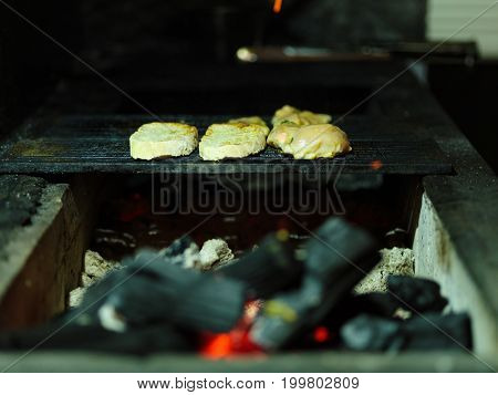 Close-up of tasty juicy pieces of grilled chicken. Fried meat on a B-B-Q blurred background. Tender smoky fillet with firewood. Outdoors, nature, cooking concept. Copy space.