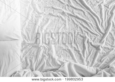 Top view bed with crumpled bed sheet, a blanket and pillows after comfort duvet sleep waking up in the morning.